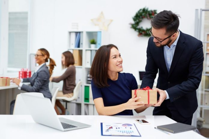 young-businessman-giving-his-colleague-christmas-345747899-696x464